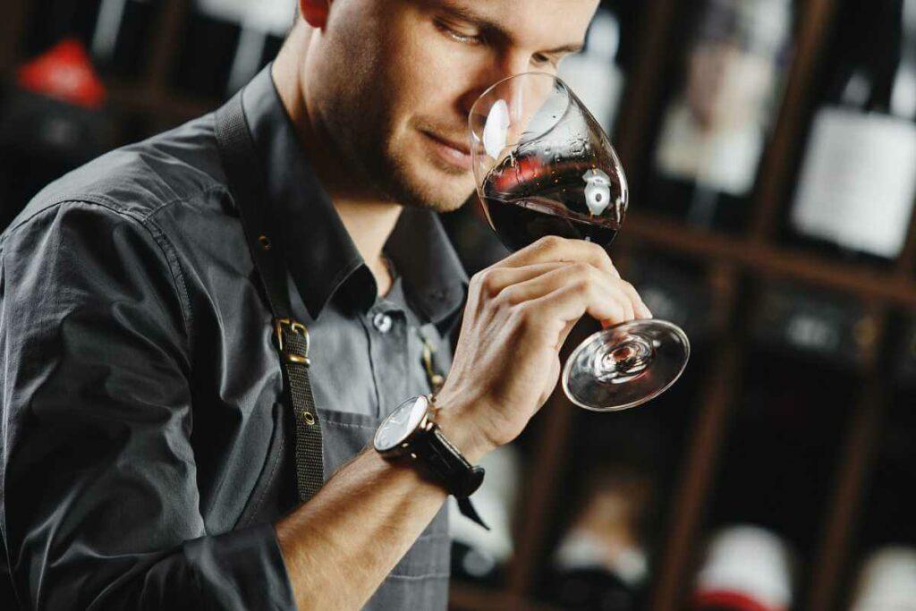 Degustacja wina w restauracji - sommelier wącha wino w kieliszku